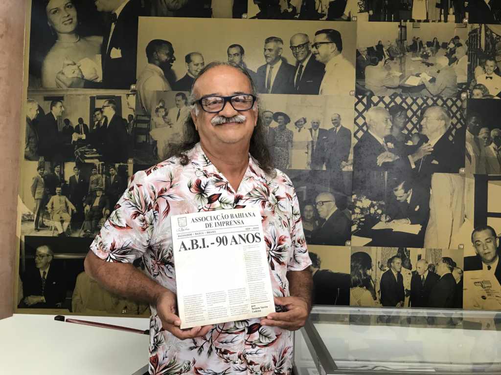 """O jornalista Nelson Cadena, a frente de um mural de fotos da Associação Bahiana de Impresa (ABI), segurando o livro """"ABI 90 Anos"""""""