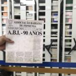 """Foto de mão segurando a capa do livro """"ABI 90 Anos"""" de Nelson Cadena"""