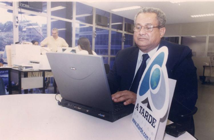 """Eliezer Varjão sentado numa mesa da redação do A TARDE, ele veste terno preto com gravata preta. A sua frente uma mesa redonda e um notebook antigo. A sua frente, diante da câmera, uma placa em PVC escrito """"A TARDE online""""."""