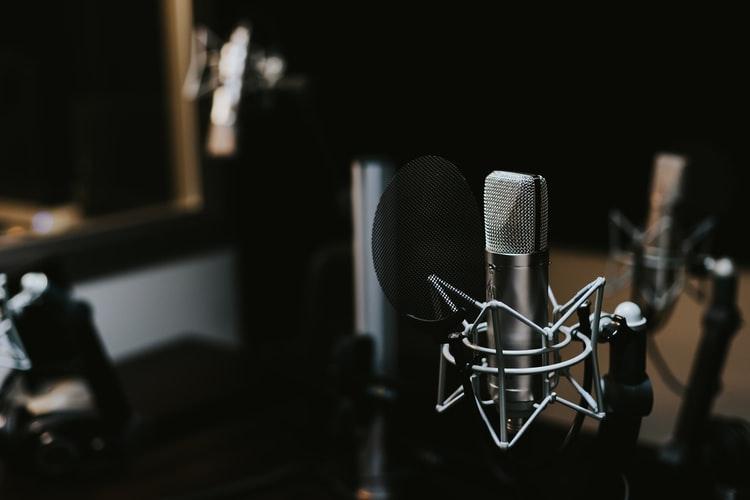 """Na foto, visualizamos um estúdio de rádio bem focalizado. Em foco aparece um microfone prateado com """"aranha"""" na parte inferior. Atrás de modo desfocado encontram-se outros microfones de mesma estrutura."""