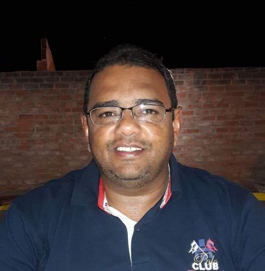 """Jean Rego veste camisa polo azul escrita a direita de quem está de frente a foto """"club"""", ele usa óculos e sorria para a câmera"""
