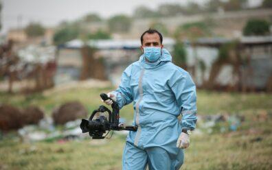 Homem vestido com trajes higiênicos, estilo de hospital na cor azul, usa máscara azul também e carrega uma câmera DSLR em mãos apoiada sob um suporte de cor preta assim como a câmera. Aparentemente encontra-se dentro de um cemitério