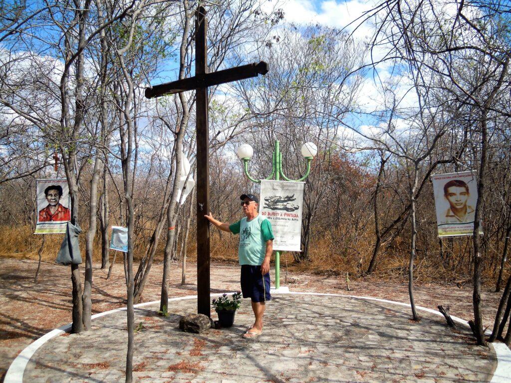 Frei Gorges, de bermuda e camisa, ao lado da cruz que marca o local onde Lamarca foi metralhado.